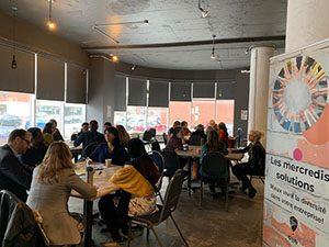 Image des invités assis en groupes sur différentes tables rondes dans le cadre de l'activité world café.