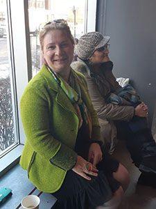 Image d'une dame habillée en vert qui pose assise lors du world café des Mercredis Solutions.